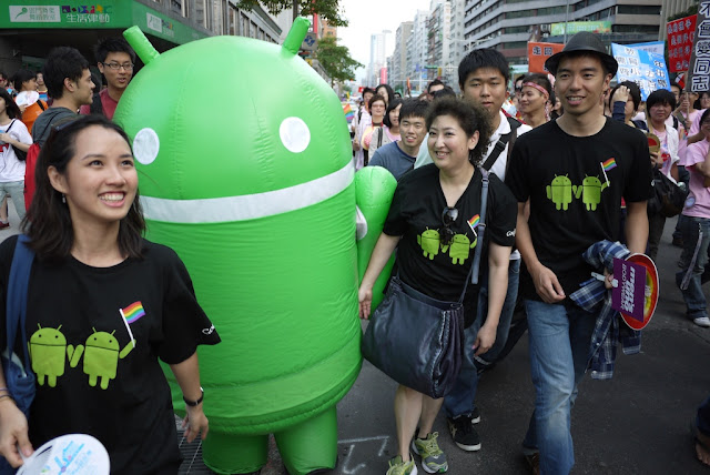 Android Robot mascot and people wearing shirts with two Android Robots holding hands and a rainbow flag at 2011 Taiwan LGBT Pride Parade