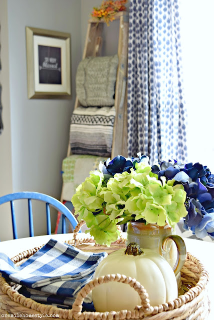 Navy blue and white fall farmhouse dining room decor with rustic blanket ladder