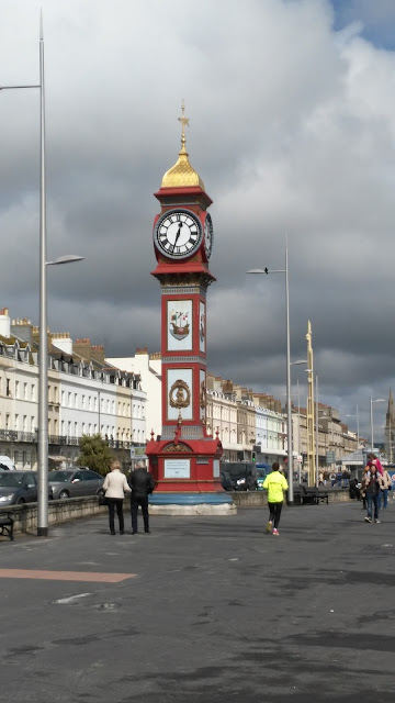 Red clock tower surrounded by people and white bulidings
