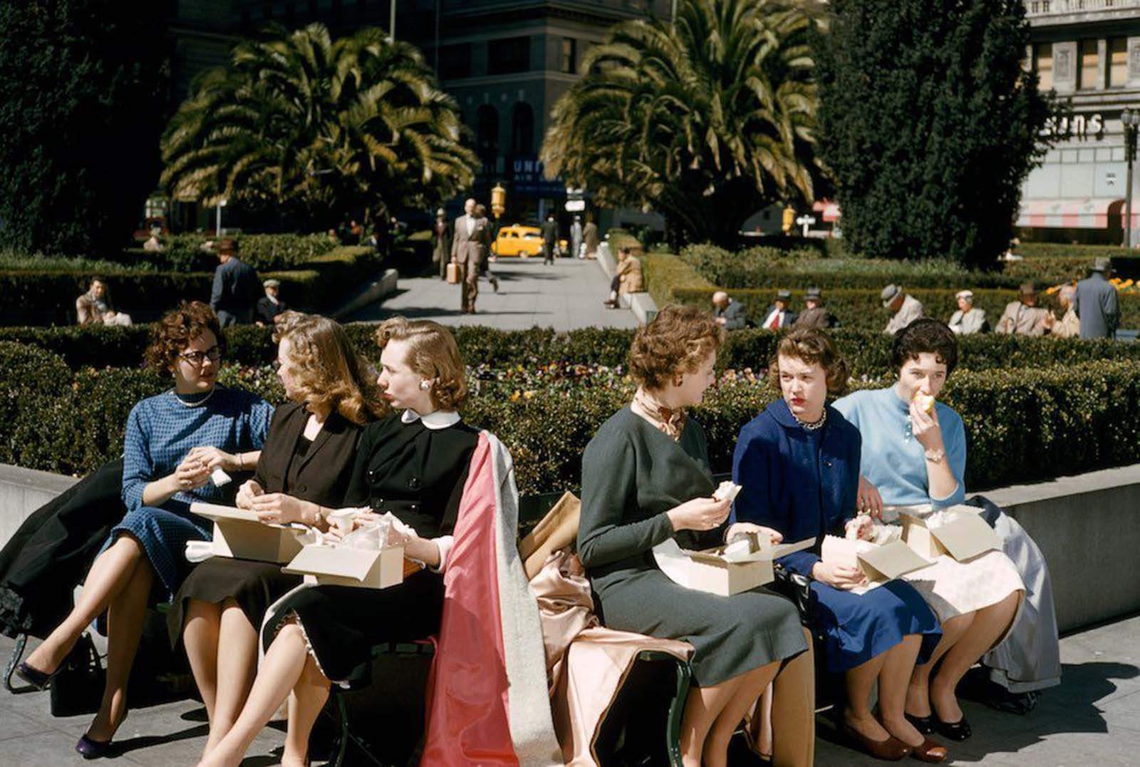 Women office workers eat boxed lunches in Union Square, San Francisco, California. Their suits are formal, in conservative colours. Their hair is worn short, typically parted at the side. All the women appear to be wearing tan stockings or hose. 1956.