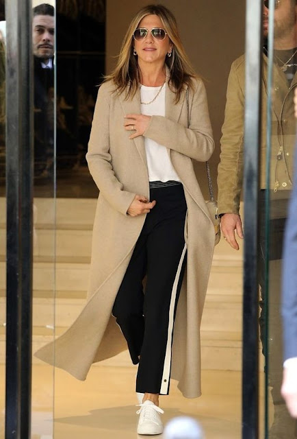 woman in long tan coat, white tee, sneakers and joggers.