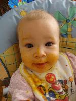 Baby vollkommen mit Brei im Gesicht beschmiert