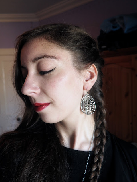 Back to Black   outfit jewellery details of large silver hoop earrings with black chain, with a side braid hairstyle and red lipstick
