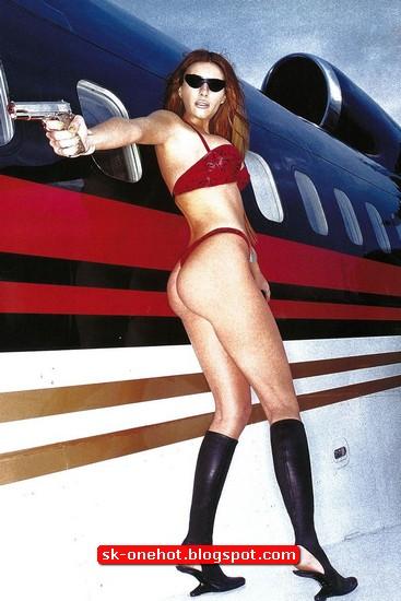 Foto Melania Trump berpakaian seksi memegang pistol disamping pesawat