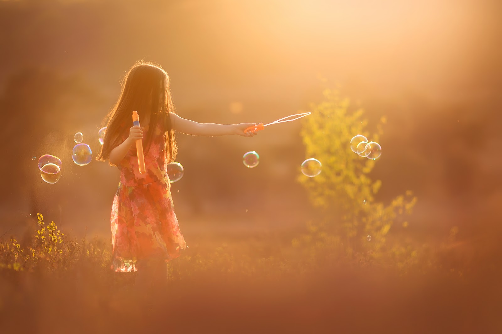 Canon portrait of a little girl with long dark hair blowing bubbles during sunset in nature by Willie Kers