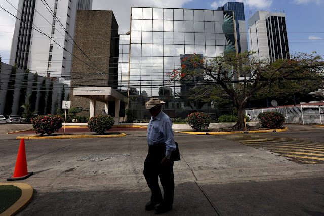 Image Attribute: A man walk by the Arango Orillac Building where the Mossack Fonseca law firm is situated at, in Panama City, April 4, 2016. REUTERS/Carlos Jasso