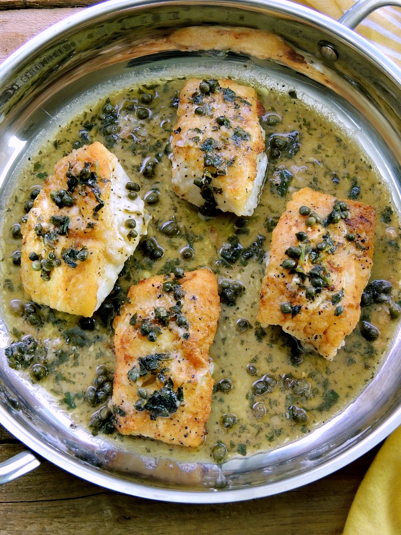 Pan-Roasted Cod with Lemon White Wine Sauce in a silver skillet.