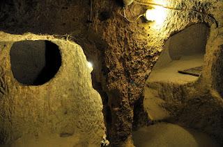 В узком коридоре кое-где есть ступеньки, вырубленные прямо в породе. Внутри царит полумрак и приятная прохлада – здесь особенно приятно побывать после уличной жары. Посетив это место, следует обратить внимание на цвета стрелок, изображенных на стенах, синие ведут к выходу, а красные – вниз, вглубь подземного города. С двух сторон от этого прохода располагаются просторные помещения – это и есть квартиры обитателей древнего города.