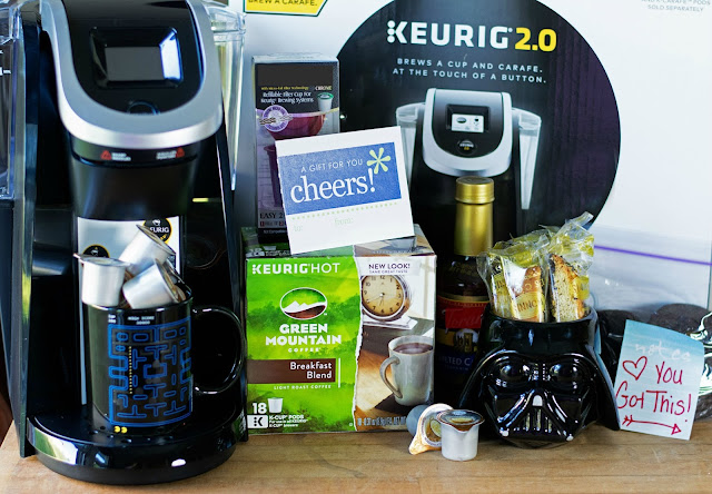 A Keurig machine, it's box and various items that make up a coffee bar.