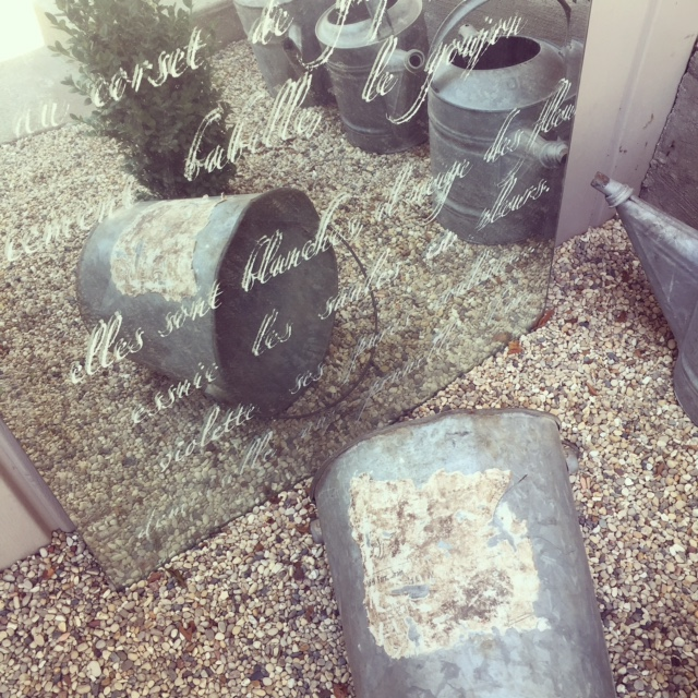 Stenciled mirror and galvanized bucket in gravel