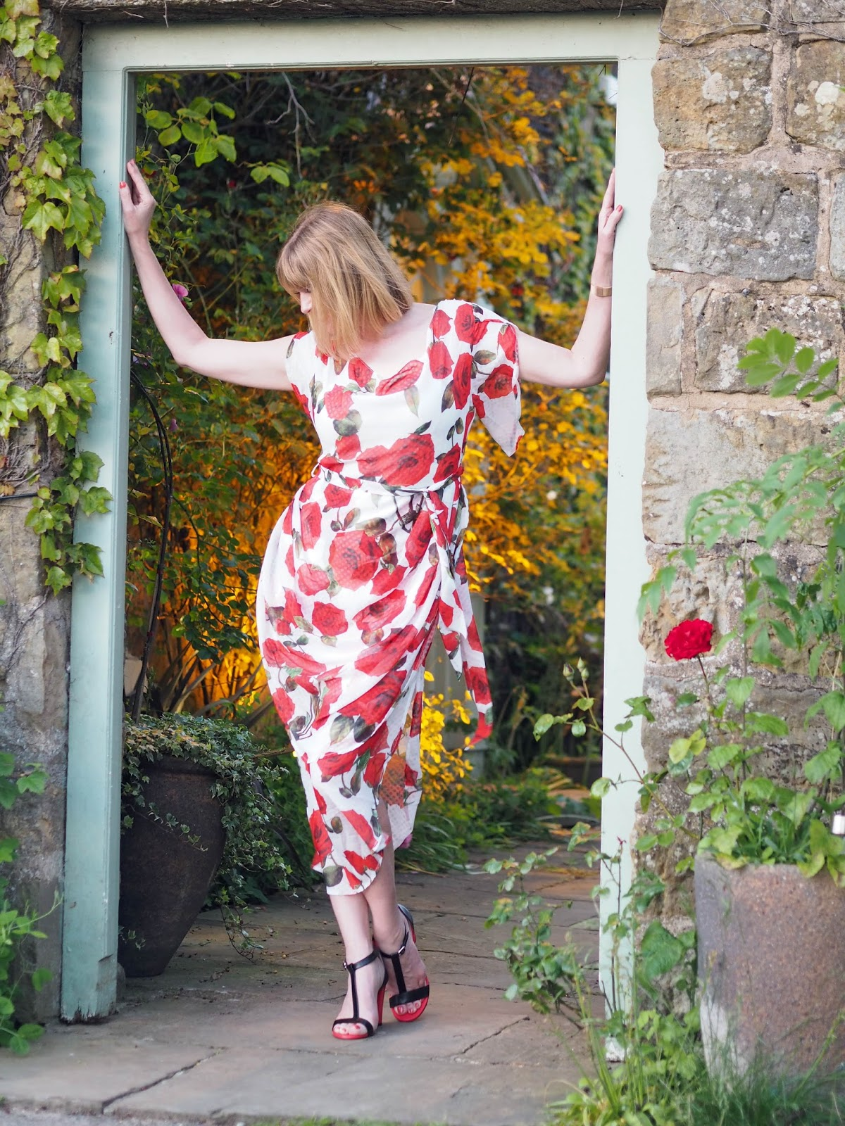 White and red floral rose draped midi dress with red and black high-heeled sandals style over 40