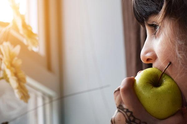 menina fazendo dieta comendo uma maca