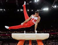 Bir erkek sporcu kulplu beygir üzerinde jimnastik yaparken
