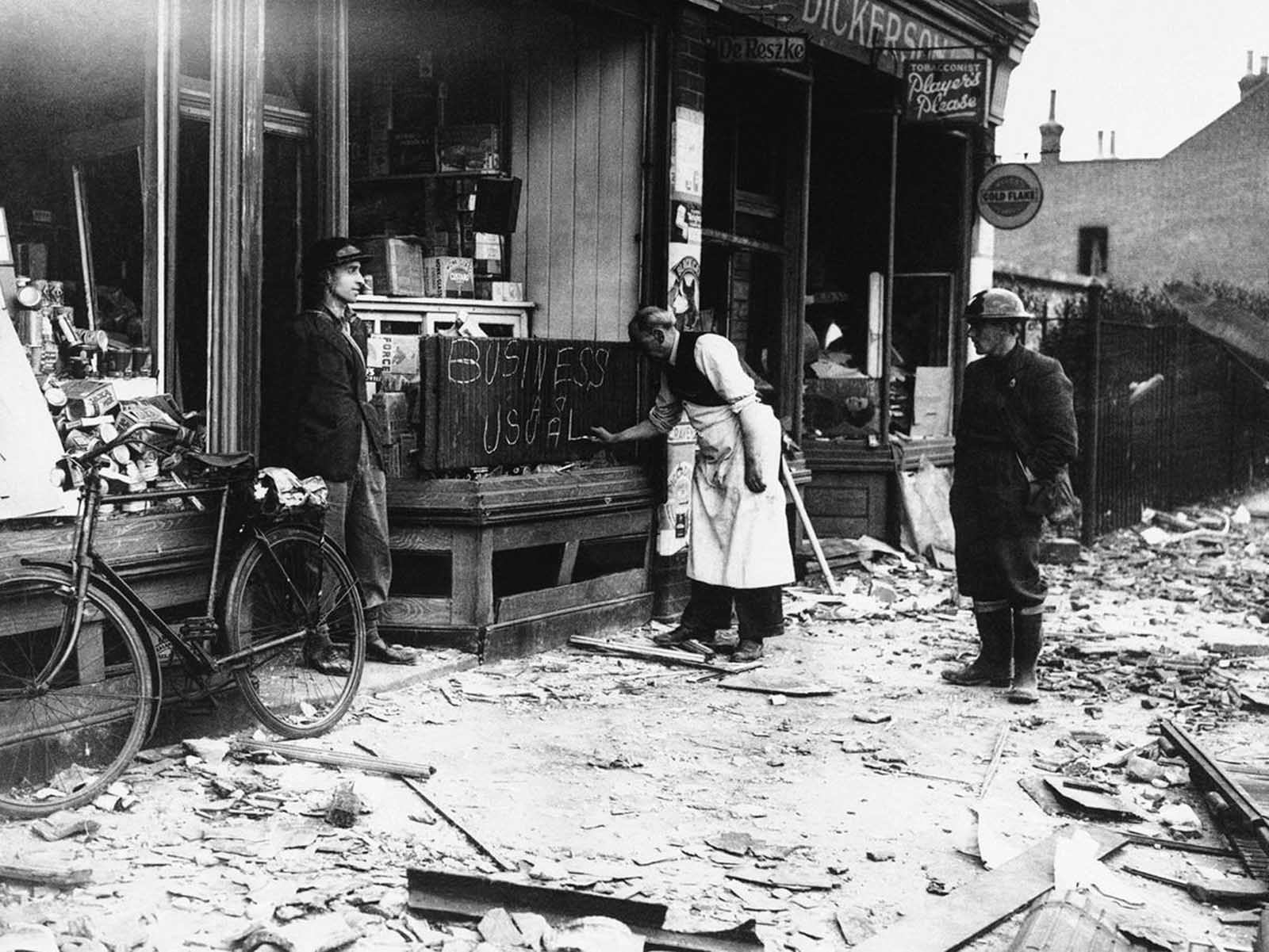Undaunted by a night of German air raids in which his store front was blasted, a shopkeeper opens up the morning after for