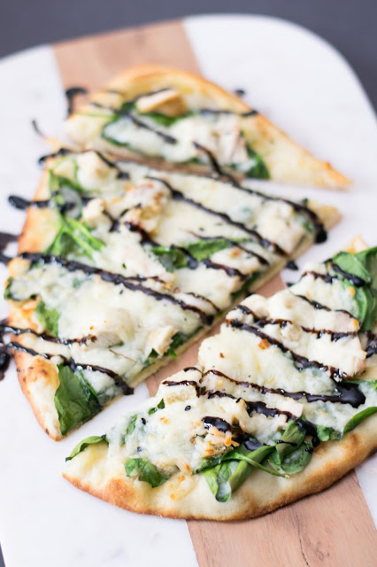 The finished Chicken and Spinach Naan Bread Pizza, cut into pieces, and drizzled with balsamic glaze.