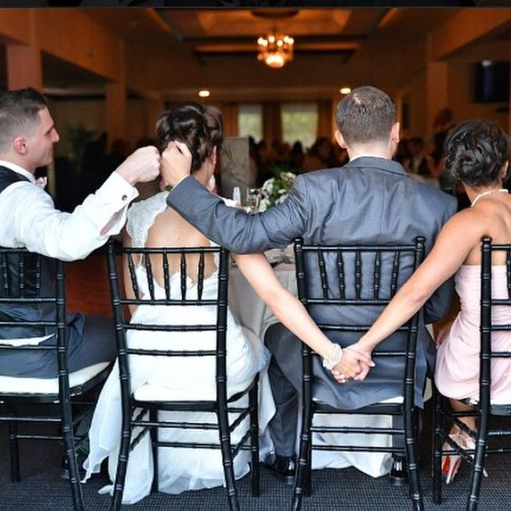 K'Mich Weddings - wedding planning - grooms check list - bridal party sitting at the table with holdings hands behind them