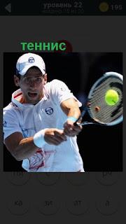 мужчина играет в теннис, отбивает мяч ракеткой