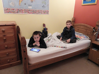 2 schoolboys on a bed playing games