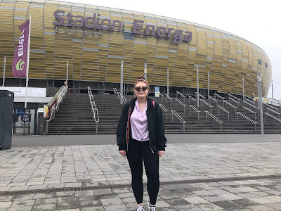 me standing in front of a large yellow round building that says Stadion Energa