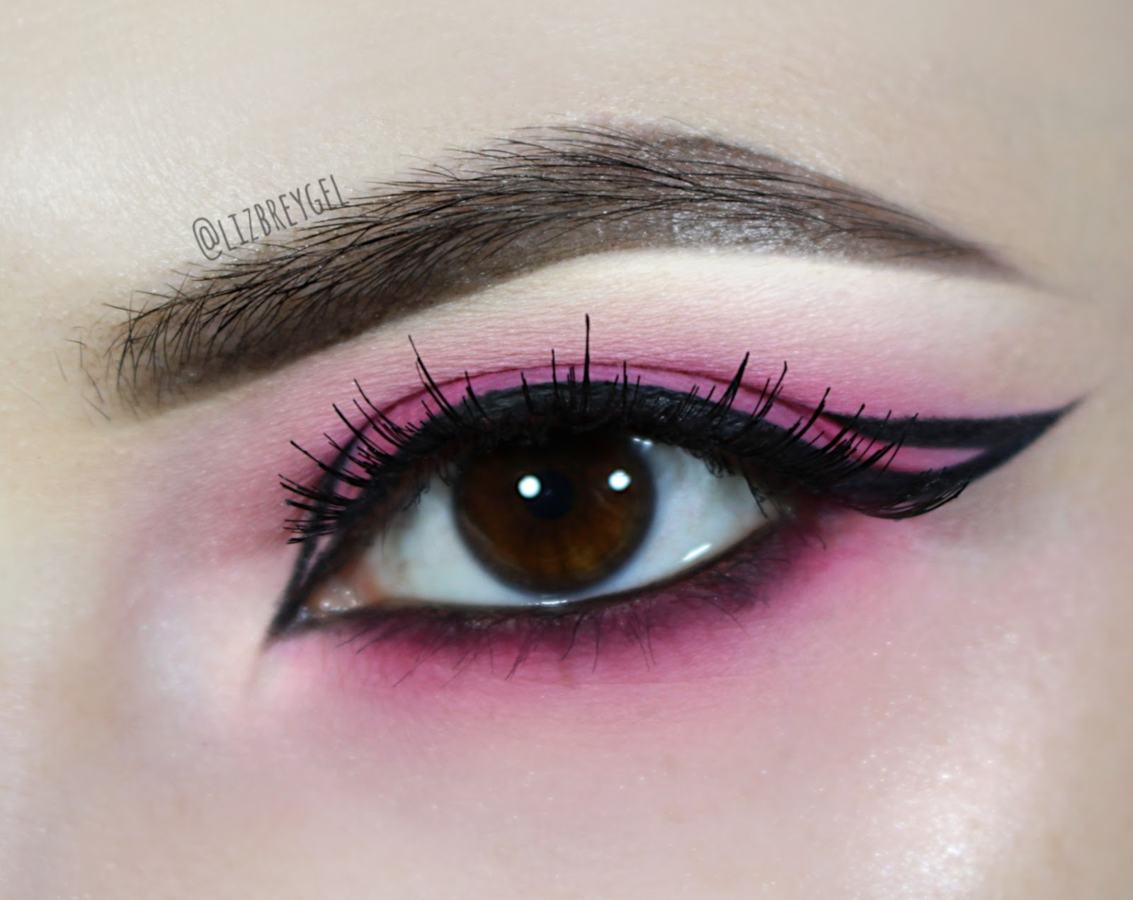 bubblegum pink and graphic eyeliner makeup look on brown eyes
