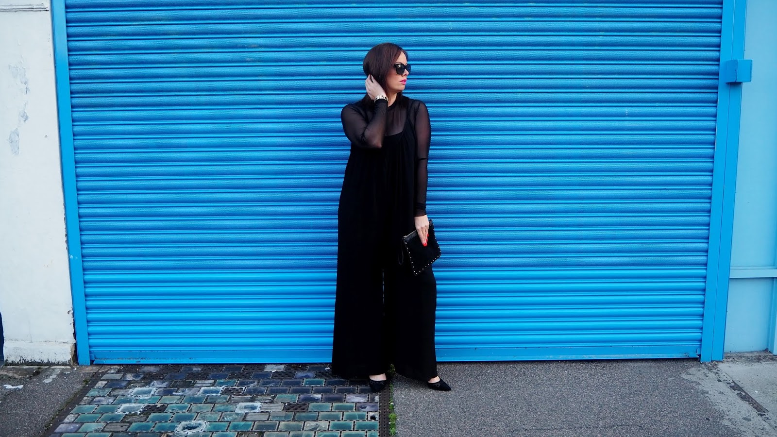 black wide leg jumpsuit layered over black mesh top