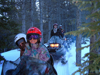 Snowmobile tour with five guests.  Riding a trail through trees on both sides.