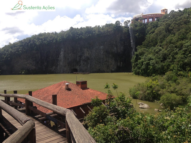 Paredão de pedra no Parque Tanguá, com túnel aberto na rocha e a passarela.