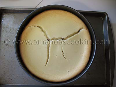 An overhead photo of a cracked cheesecake.