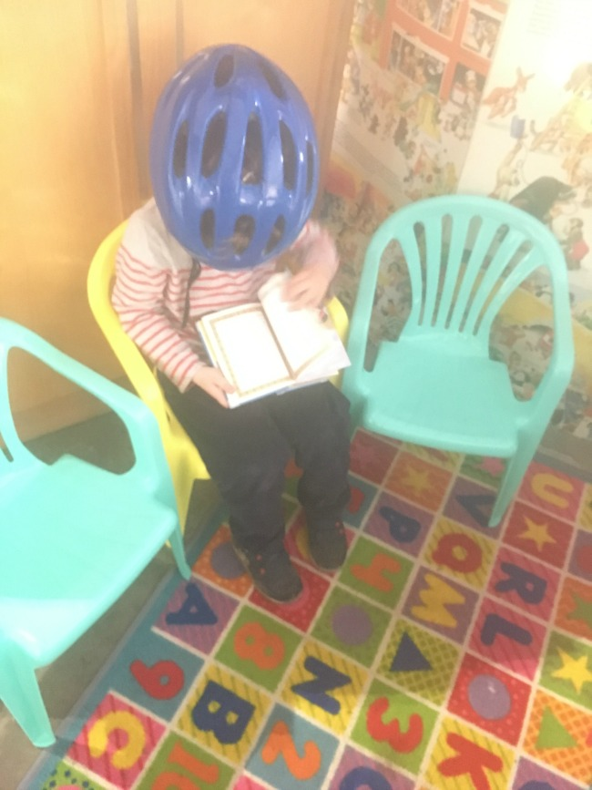toddler-reading-book-wearing-his-helmet-at-at-Tredegar-park