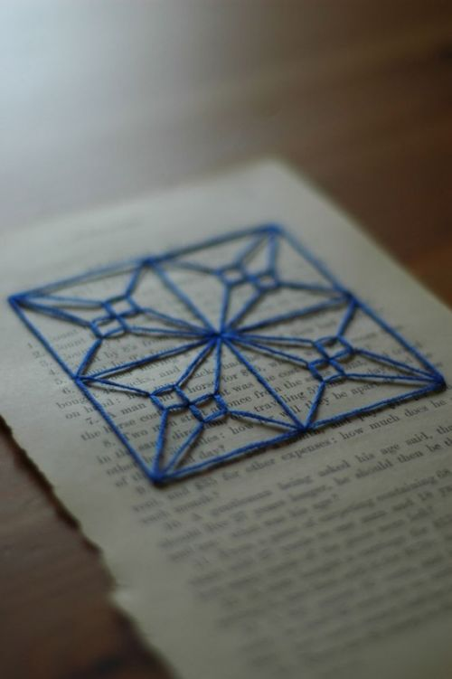 blue embroidery on vintage book page