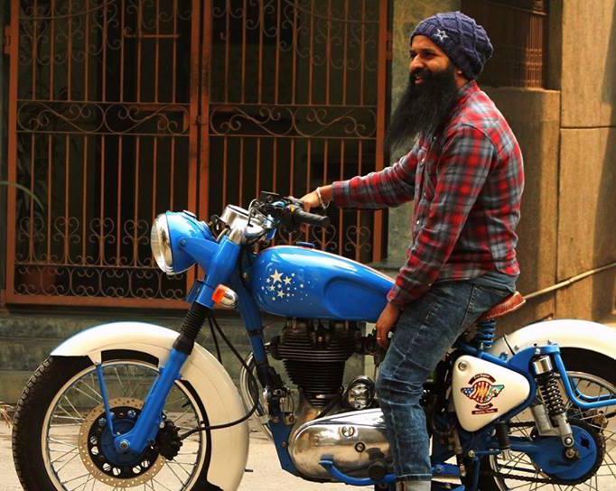 Man sitting on Royal Enfield motorcycle.