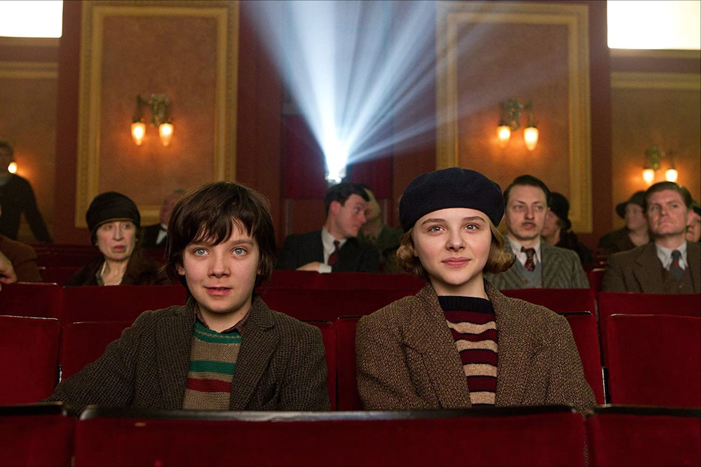 Asa Butterfield and Chloe Grace Moretz seated in movie theater, grinning, directly facing out at the viewer