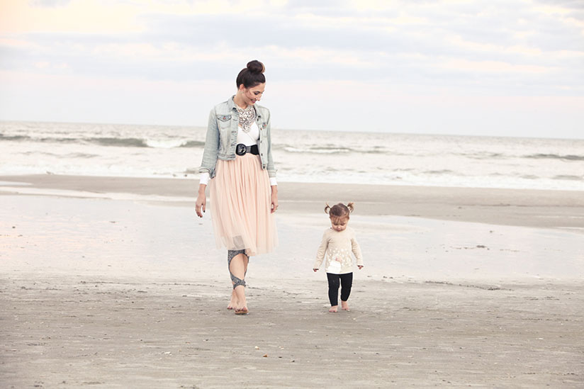 Amy West and daughter walk on the beach