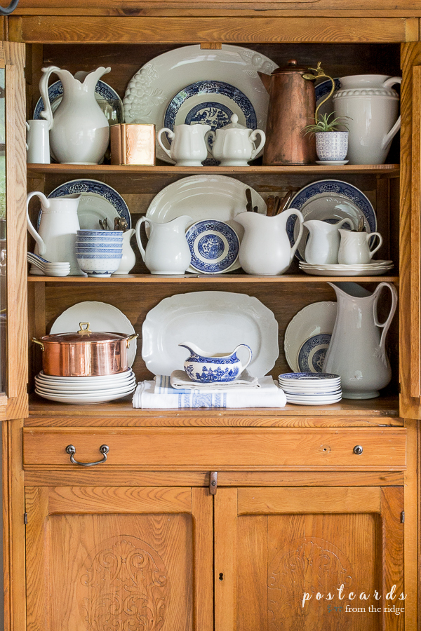 blue willow dishes and white ironstone in an antique oak hutch