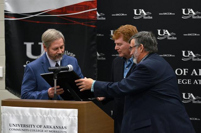 three men at podium
