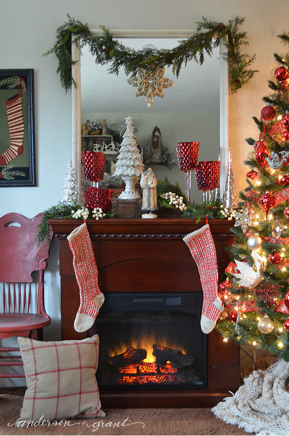 Christmas mantel decorated with reds and creams | www.andersonandgrant.com