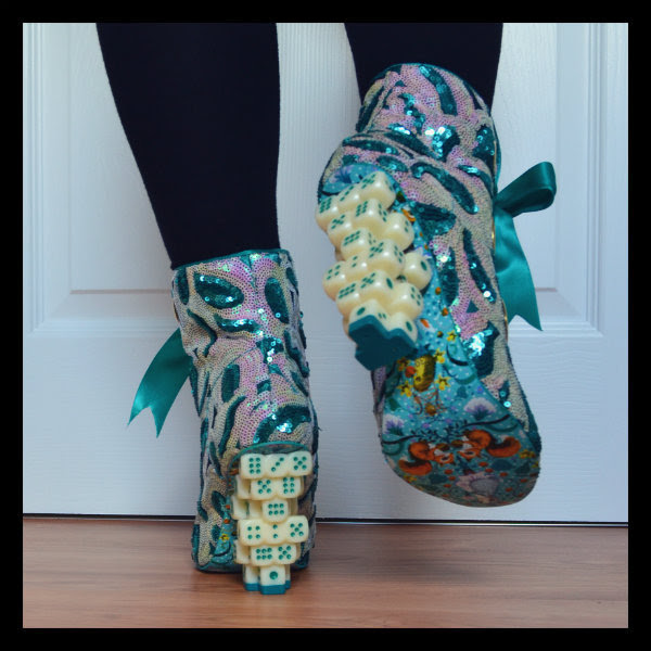 back view of feet in dice heeled boots with one leg lifted to show printed sole of boot