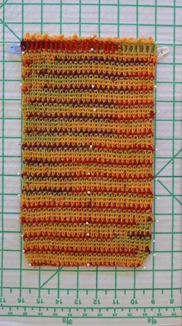 The crocheted bag is laying flat and held against the blocking board with pins.