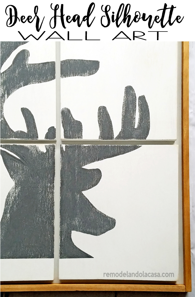 white and grey deer head silhouette with a wooden frame