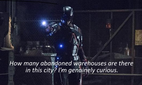 A screenshot of Ray Palmer, dressed as the Atom in futuristic red armour, standing in an abandoned warehouse. The caption reads, How many abandoned warehouses are there in this city? I'm genuinely curious.