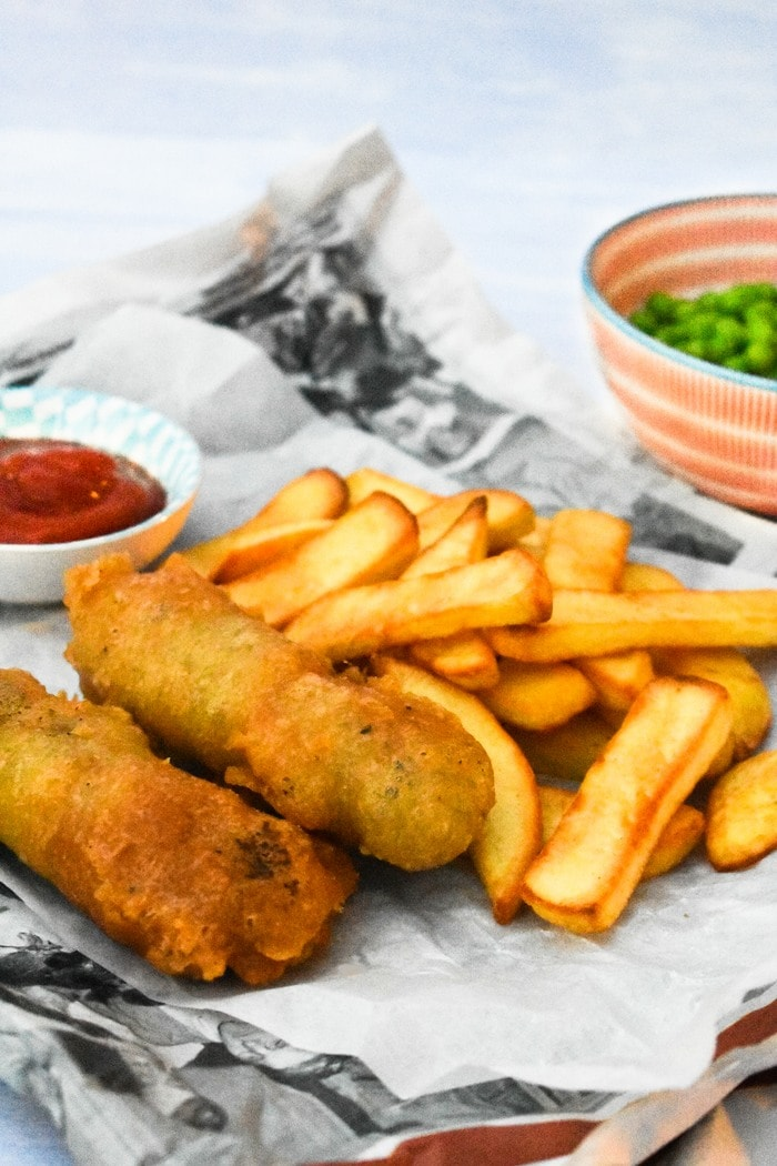 Vegan Chip Shop Sausage Supper in newspaper with chips, peas and ketchup