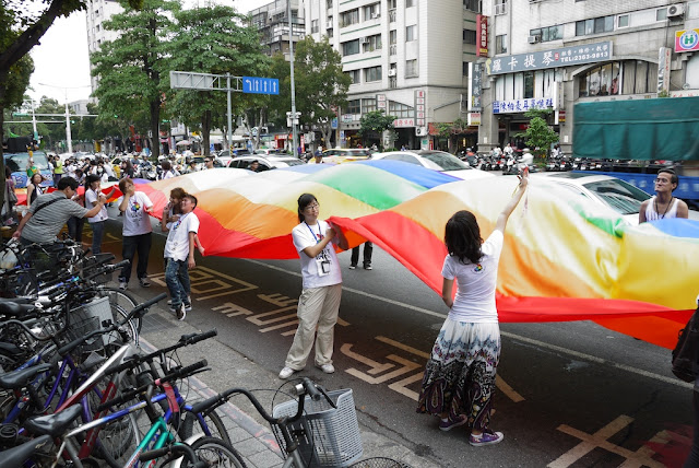 people holding up a large waving rainbow banner at the 2011 Taiwan LGBT Pride Parade