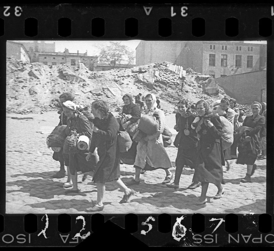 These 32 Pictures Had Been Buried For Years. The Reason Is Heart-Breaking - 1940-1944: A Group Of Women With Sacks And Pails, Walking Past Synagogue Ruins Heading For Deportation