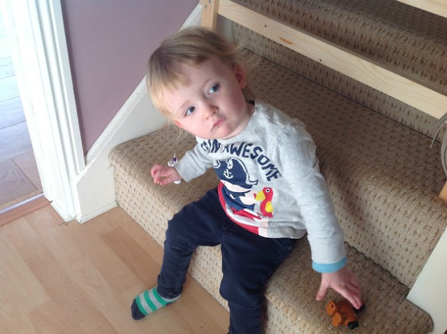toddler sat on bottom stair with head to one side looking innocent