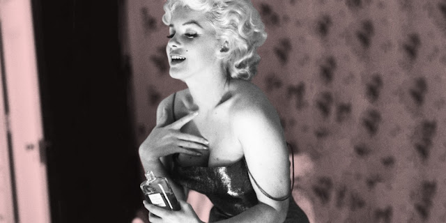 a picture of Manilyn Monroe holding a bottle of perfume