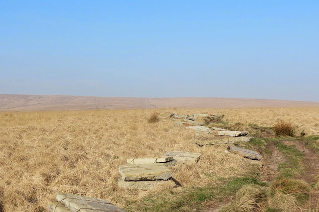 An expanse of moorland as far as the eye can see - pale grass under blue sky. A path of bare earth cuts through the grass and various stones lie at the side of it, ready to be laid.