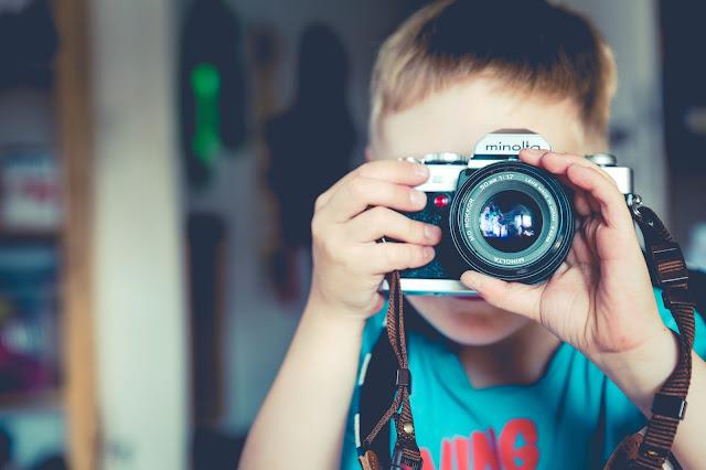 Niño que toma fotos en cámara reflex