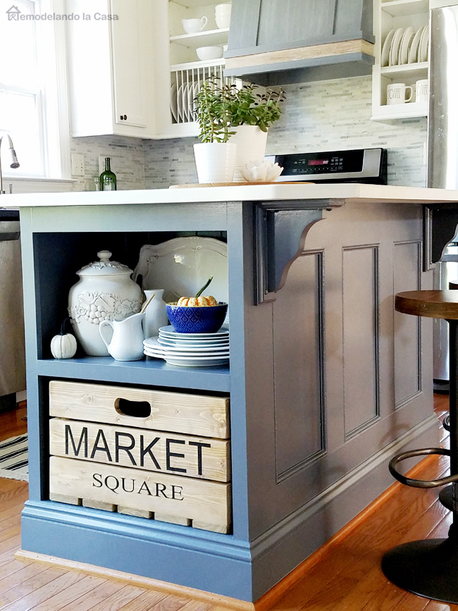 Grey kitchen island with wooden crate.
