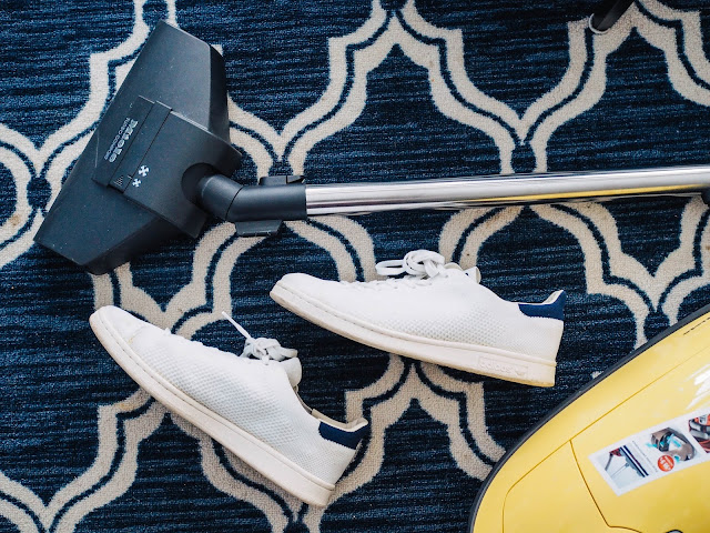 Vacuum being used on rug with a pair of trainers laid in the way