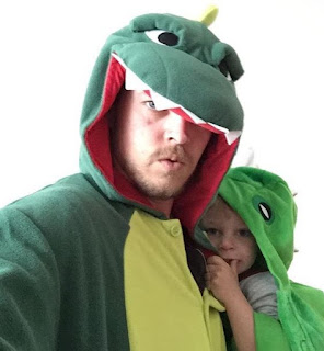 Father and son wearing dinosaur costumes